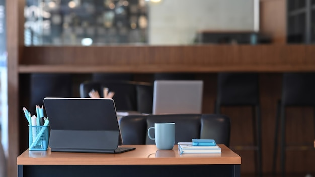 Local de trabalho do designer criativo com um computador tablet, xícara de café, caderno e artigos de papelaria na mesa de madeira.