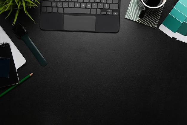 Local de trabalho do designer gráfico com tablet, xícara de café, caderno, amostra de cor e espaço de cópia em couro preto.
