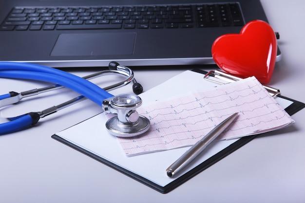 Local de trabalho do doutor com portátil, estetoscópio, prescrição de rx e coração e caderno vermelhos na tabela.