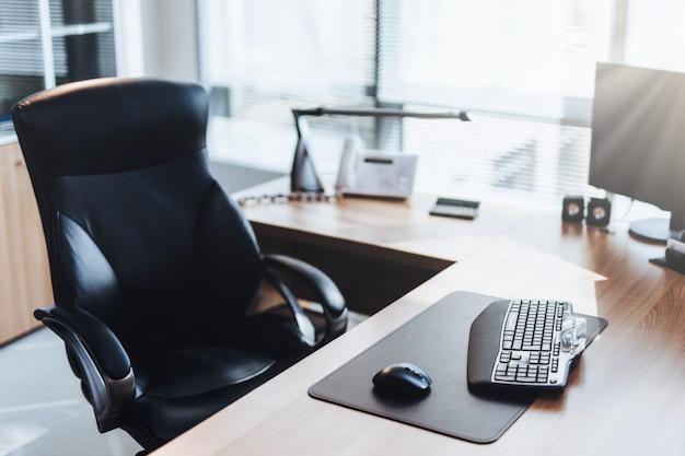 Local de trabalho do empresário: computador, mesa de madeira e cadeira no armário