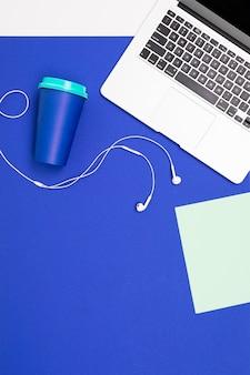 Local de trabalho do escritório. fones de ouvido, notebook, caneca e teclado de notebook mentem na superfície azul