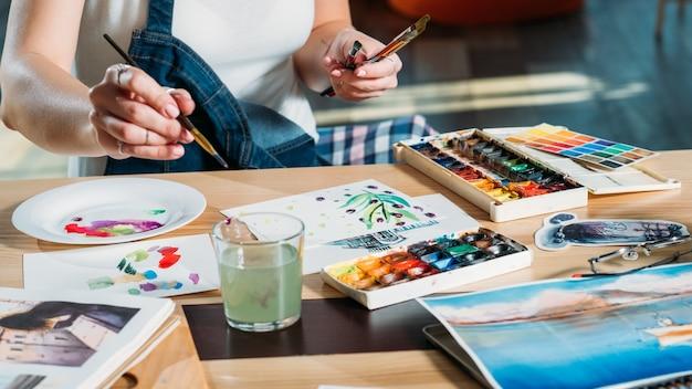 Local de trabalho do estúdio. passatempo de pintura. mulher fazendo primeiras pinceladas com esboços e materiais de paleta ao redor.