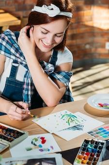 Local de trabalho do estúdio. passatempo de pintura. mulher ruiva sorridente fazendo primeiras pinceladas com materiais de paleta ao redor.