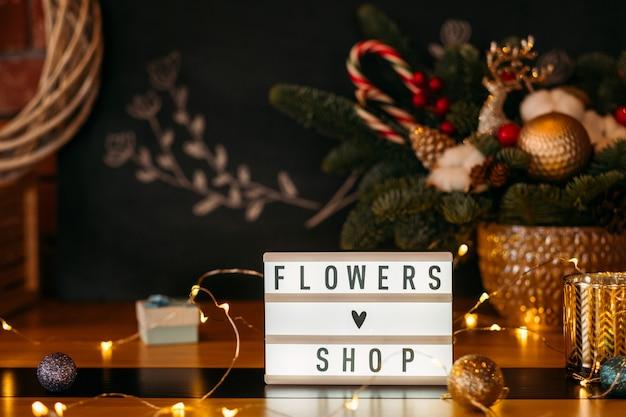 Local de trabalho do florista. placa de sinal de loja de flores e luzes de fada sobre arranjo de árvore de abeto de borrão.