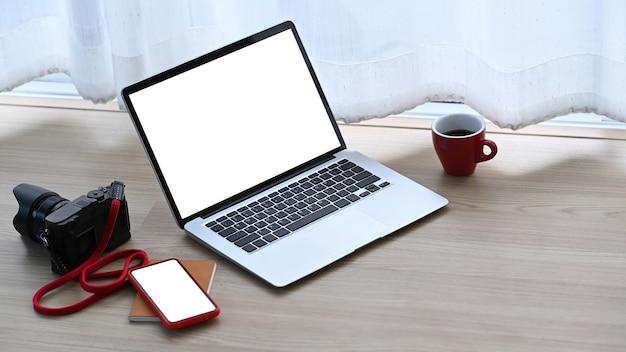 Local de trabalho do fotógrafo com notebook, smartphone, câmera e xícara de café no chão de madeira no escritório doméstico.