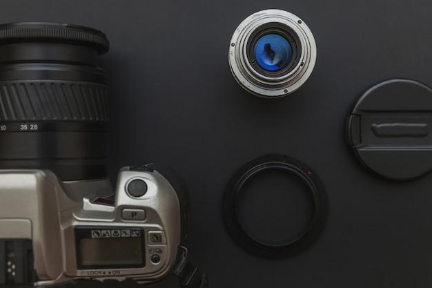 Local de trabalho do fotógrafo com sistema de câmera dslr e lente no fundo da mesa de preto escuro. conceito de fotografia de viagens passatempo. vista plana leiga cópia espaço.