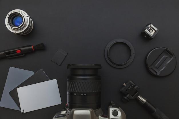 Local de trabalho do fotógrafo com sistema de câmera dslr, kit de limpeza da câmera, lente e acessório da câmera no fundo da mesa de preto escuro. conceito de fotografia de viagens passatempo. vista plana leiga cópia espaço.
