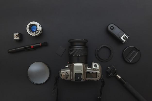 Local de trabalho do fotógrafo com sistema de câmera dslr, kit de limpeza de câmera, lente e acessório de câmera na mesa de preto escuro. conceito de fotografia de viagens passatempo. vista plana leiga cópia espaço.