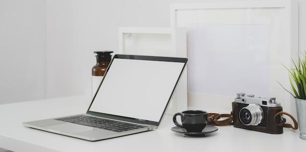 Local de trabalho do fotógrafo moderno com laptop de tela em branco e material de escritório