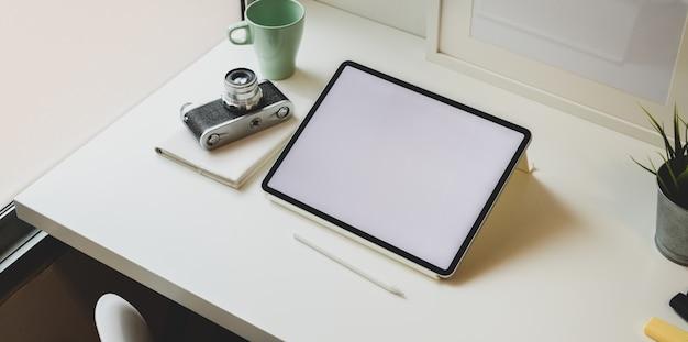 Local de trabalho do fotógrafo na moda com tablet de tela em branco