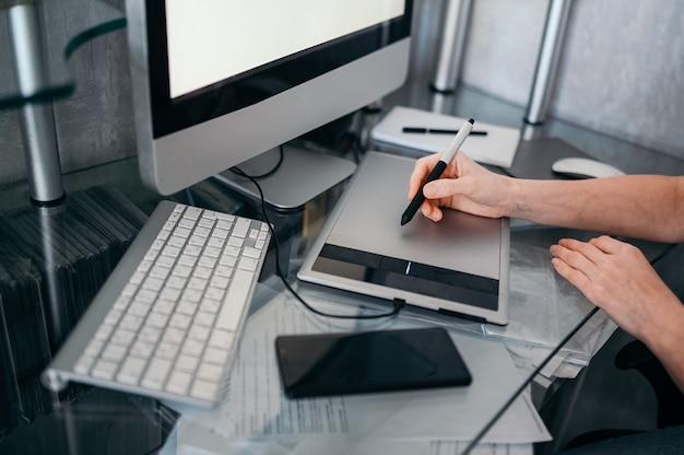 Local de trabalho do fotógrafo ou designer gráfico. designer criativo mãos trabalhando no laptop com tablet gráfico. monitor de computador, teclado, caderno vazio, mouse, smartphone