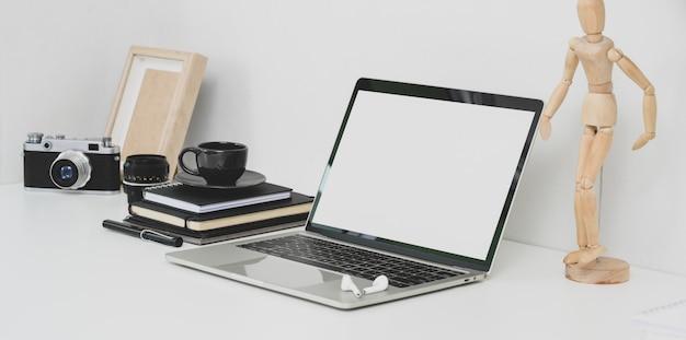 Local de trabalho do fotógrafo profissional com laptop de tela em branco aberto, câmera e material de escritório