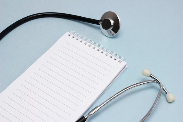 Local de trabalho do médico. um estetoscópio e um caderno para escrever com uma página em branco. conceito de medicina e saúde.