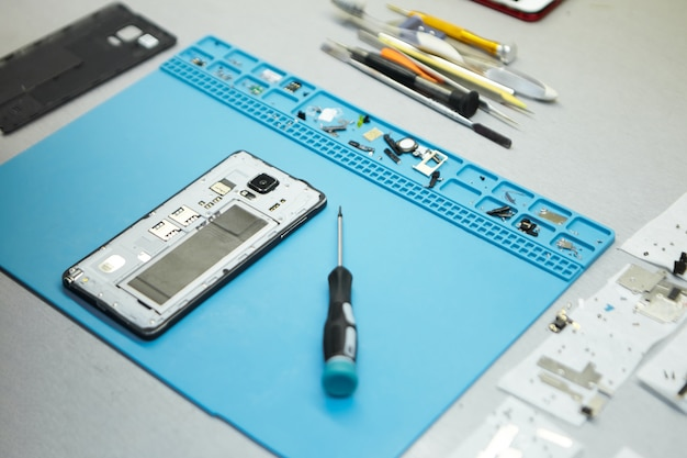 Local de trabalho do reparador com telefone celular e ferramentas especiais na mesa