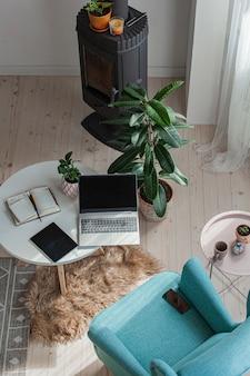 Local de trabalho doméstico perto da lareira, poltrona, laptop, tablet na mesa, vista superior