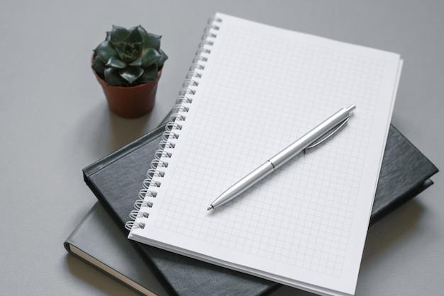 Local de trabalho elegante. cadernos e agendas em uma área de trabalho cinza com uma caneta, suculenta.