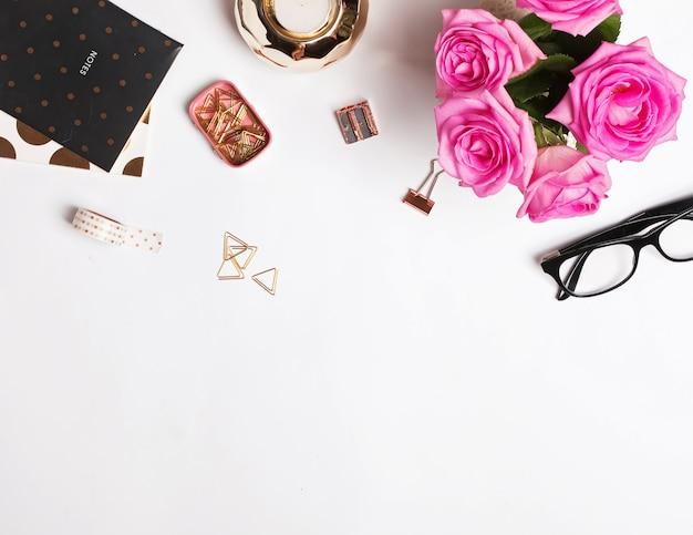 Local de trabalho elegante com rosas cor de rosa e pequenos acessórios em fundo branco, vista superior