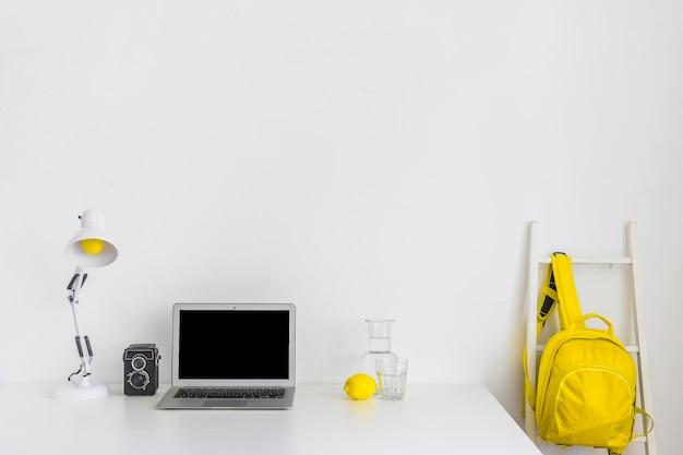 Local de trabalho elegante nas cores brancas e amarelas com mochila e laptop