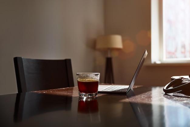 Local de trabalho em casa com laptop, copo de bebida quente na mesa perto da janela no pôr do sol ou nascer do sol. trabalhando em casa, escritório em casa.
