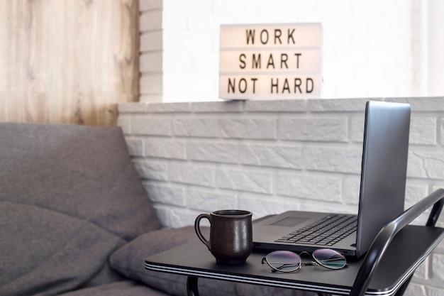Local de trabalho em casa de um freelancer em uma mesa preta elegante perto do sofá e a parede de tijolo