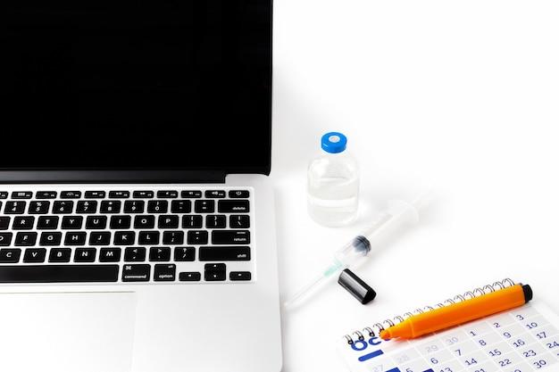 Local de trabalho em quarentena com um computador, uma seringa, uma vacina, um marcador e um calendário como símbolo de vacinação para proteger as pessoas. no fundo branco