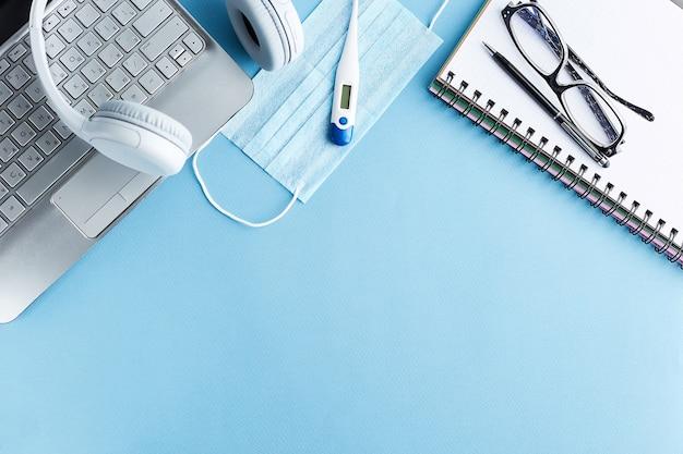 Local de trabalho em quarentena. local de trabalho de trabalho em casa. trabalho remoto em casa. papel branco em branco e caneta preta, máscara médica, termômetro, fones de ouvido e laptop