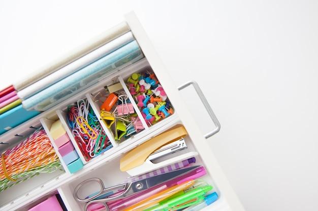 Local de trabalho feminino branco. um método para armazenar artigos de papelaria de forma organizada. canetas coloridas elegantes, grampeador, lápis.