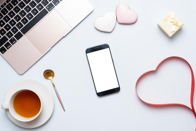 Local de trabalho feminino desktop com coração vermelho, laptop, telefone móvel. conceito de composição do dia dos namorados