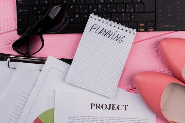 Local de trabalho feminino estilizado com bloco de notas de teclado e vários papéis