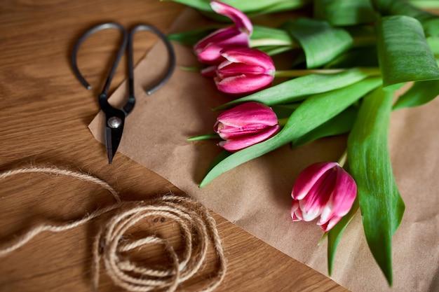 Local de trabalho florístico com papel artesanal, barbante, arranjando buquê de tulipas cor de rosa na mesa de madeira, hobby, faça você mesmo, conceito de presente de primavera, de cima.