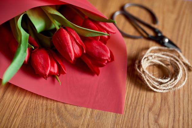 Local de trabalho florístico com papel ofício, barbante, arranjando buquê de tulipas vermelhas na mesa de madeira, hobby, faça você mesmo, conceito de presente de primavera, de cima.