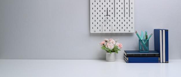 Local de trabalho freelance com livros, artigos de papelaria, vaso de flores e espaço de cópia na mesa branca