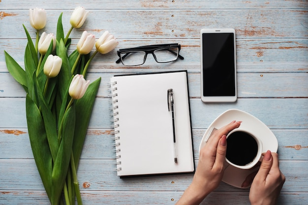 Local de trabalho freelance de espaços em branco de primavera com um buquê de tulipas brancas, smartphone e uma xícara de café nas mãos, sobre um fundo azul de madeira