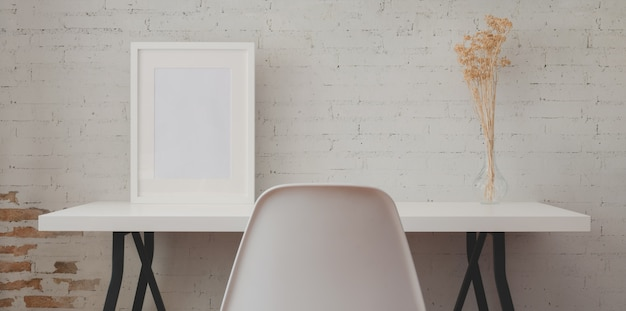 Local de trabalho loft com mesa de madeira branca e quadro de maquete e vaso na parede de tijolos antigos