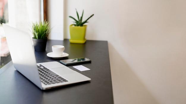 Local de trabalho minimalista com laptop e plantas