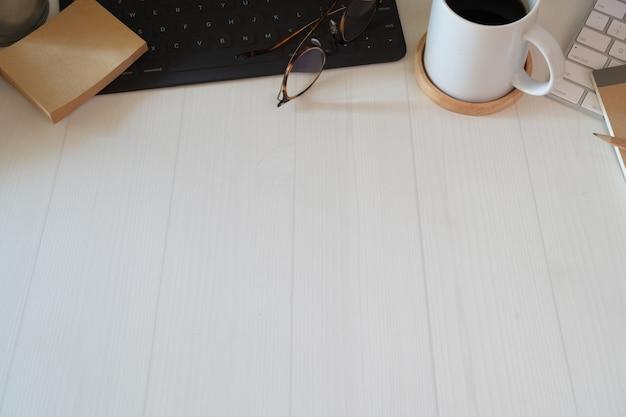 Local de trabalho minimalista elegante com teclado, notebook, material de escritório e espaço de cópia