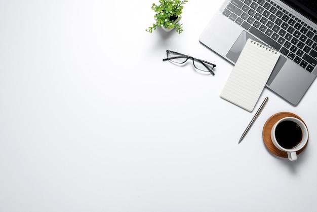 Local de trabalho minimalista moderno com laptop canecas óculos notebook trabalho vista superior. copie a área de colagem plana.