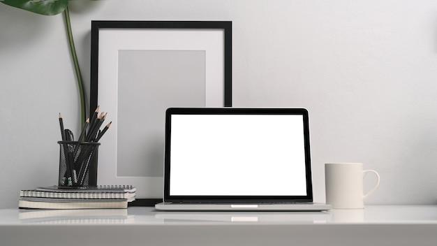 Local de trabalho mínimo com computador laptop, porta-lápis, moldura preta vazia e xícara de café na mesa branca