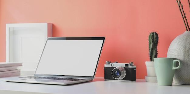 Local de trabalho mínimo com laptop de tela em branco aberto