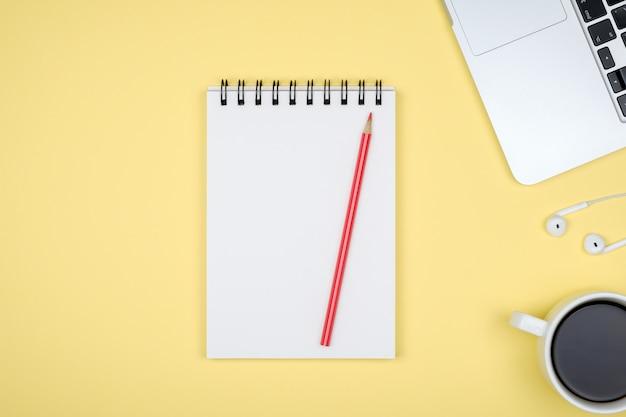 Local de trabalho mínimo com laptop e bloco de notas em branco