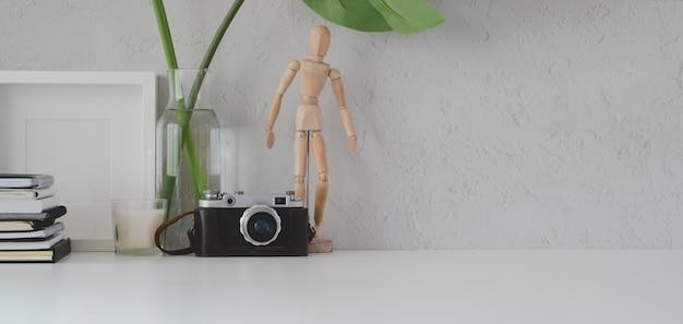 Local de trabalho mínimo com moldura, câmera e material de escritório na mesa branca