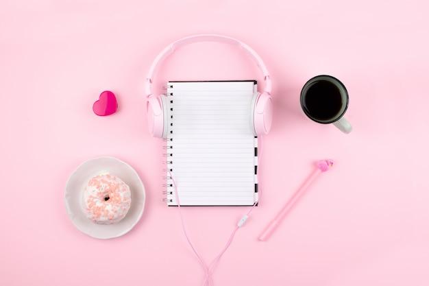 Local de trabalho mínimo com o bloco de notas em branco, fones de ouvido