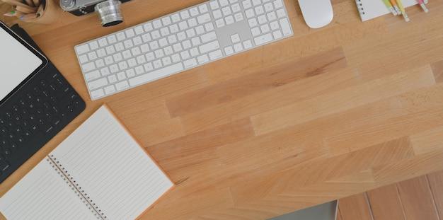Local de trabalho mínimo com tablet, caderno em branco e material de escritório na mesa de madeira com espaço de cópia