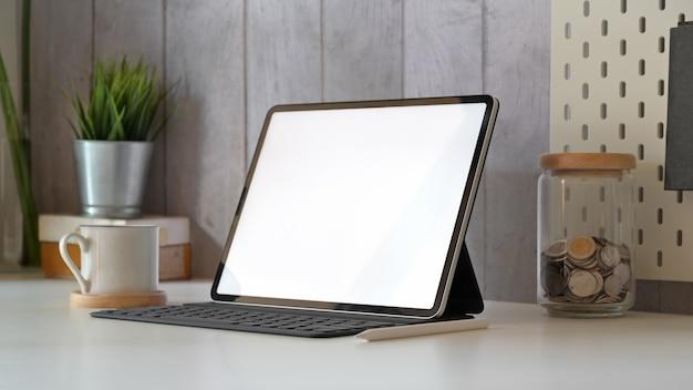 Local de trabalho mínimo com tablet de tela em branco de maquete