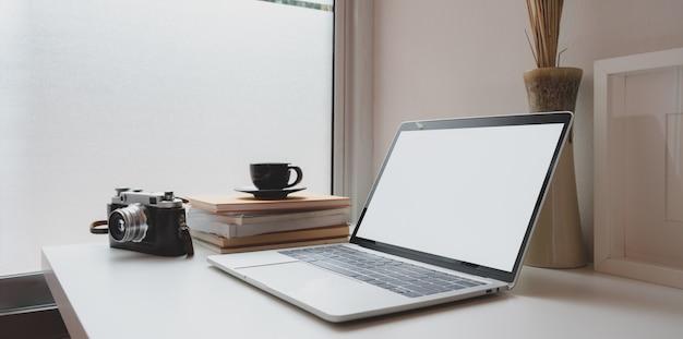 Local de trabalho mínimo do fotógrafo com laptop de tela em branco aberto, câmera vintage e uma xícara de café
