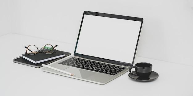 Local de trabalho mínimo do fotógrafo com laptop de tela em branco aberto