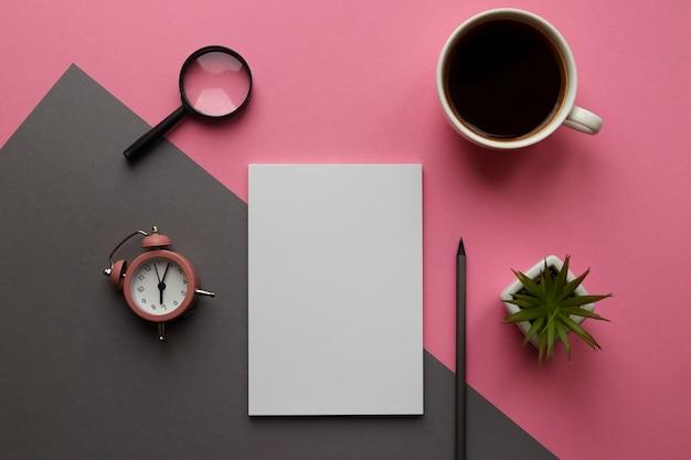 Local de trabalho moderno com bloco de notas, lápis, planta, xícara de café, lupa e despertador