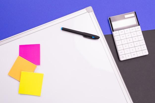 Local de trabalho moderno com caderno, caneta e calculadora isolado azul preto