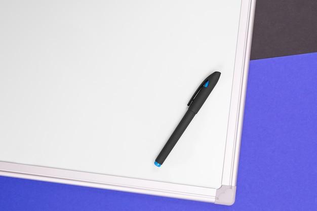 Local de trabalho moderno com caderno, caneta e calculadora isolados no fundo preto azul