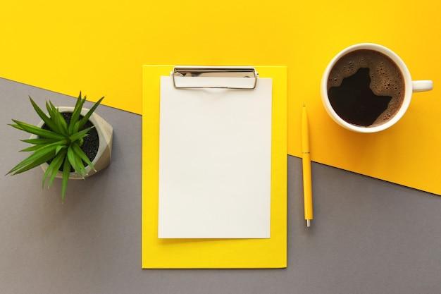 Local de trabalho moderno com caneta para prancheta para smartphone xícara de café e planta suculenta na mesa de escritório amarela e cinza